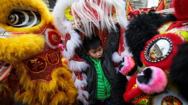 A young performer prepares to take part in a Chinese New Year parade