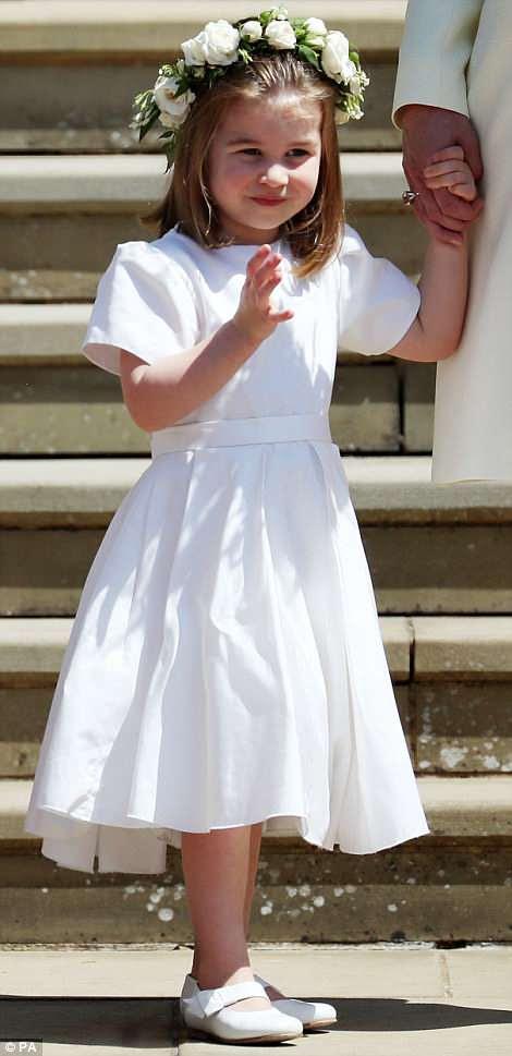 En la imagen: una adorable princesa Charlotte corta una linda figura con un vestido blanco de dama de honor completo con una guirnalda de flores mientras saluda a los fotógrafos en los escalones de la capilla de San Jorge