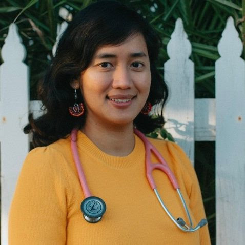 Dr. Thinn Thinn Khine stands in front of a white picket fence with a stethoscope draped over her neck.