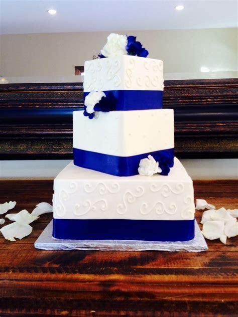 Wedding cake  Blue ribbon  White flowers.   Wedding