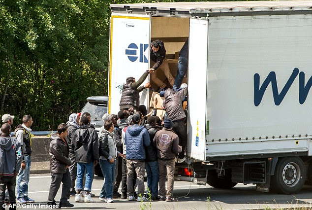 Migrants climb in the back of a lorry on the  highway leading to the Eurotunnel  in Calais, northern France