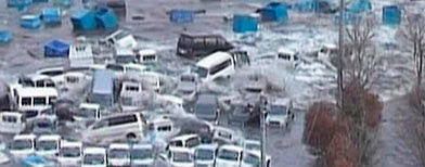 Cars and containers are swept by a tsunami wave in Miyako (Reuters/TBS via Reuters TV)