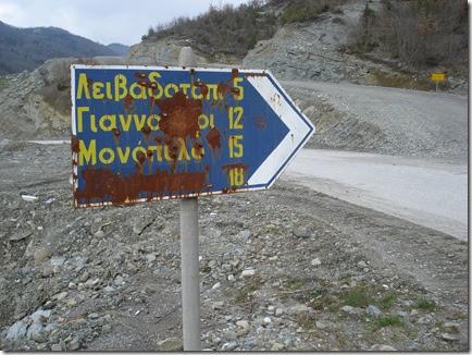 Μια πινακίδα υποδεικνύει ποια χωριά θα συναντήσεις αν ακολουθήσεις αυτό τον χωματόδρομο. Το τελευταίο έχει αφαιρεθεί βίαια γδέρνοντας τη λαμαρίνα με αιχμηρό αντικείμενο. Από «λάθος» είχε γραφτεί «Σλήμνιτσα».