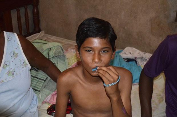 Luan Correa, de 12 anos, beija terço que usou durante toda a internação  (Foto: John Pacheco/G1)