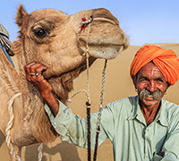 man standing next to a camel