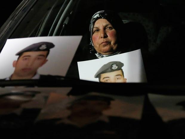 Mãe do piloto sequestrado pelo Estado Islâmico Muath al-Kasaesbeh exibe fotos do filho durante uma manifestação em frente à casa do primeiro-ministro em Amã. Ela exige que o governo jordaniano negocie com o Estado Islâmico para o liberação de Muath (Foto: Muhammad Hamed/Reuters)