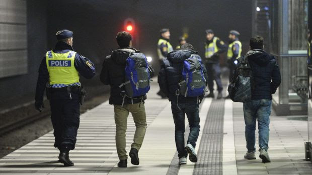 The police escort three men from a train at Hyllie station outside Malmo, Sweden.  Interior Minister Anders Ygeman says ...