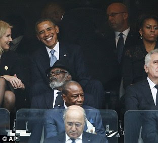 They then share a joke during the poignant memorial to Nelson Mandela