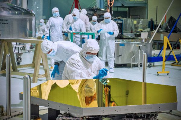 Technicians inspect one of the Jame Webb Space Telescope's (JWST) first two mirror segments in a clean room at the Goddard Space Flight Center in Maryland.