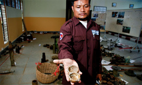 Ngoun Thy of the Cambodian Mine Action Centre holds the remnants of a cluster submunition
