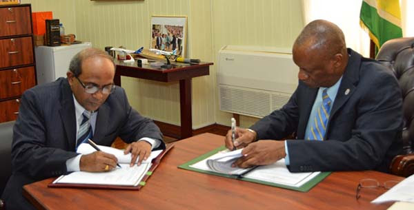 Indian High Commissioner to Guyana, Venkatachalam Mahalingam (left), and Minister of State, Joseph Harmon signing the Memorandum of Understanding.