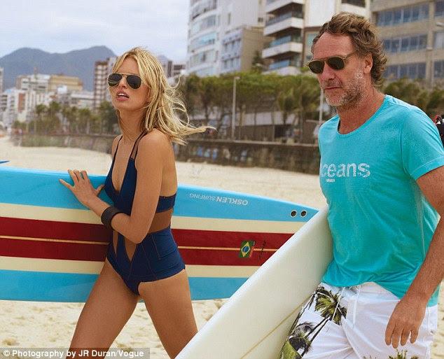 Surf é up: A mãe-de-um tenta a sua sorte no surf, as ondas batendo numa praia brasileira em um azul marinho e bege de uma peça