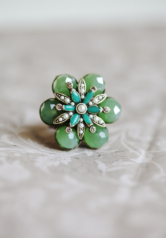 "Rejuvenating Heart Ring By Ollipop 33.99 at shopruche.com. Lovely kiwi colored stones adorned with a floral inlay filled with mini faux pearls and teal petals. Adjustable band.  Pendant is approximately 1.5"" wide."