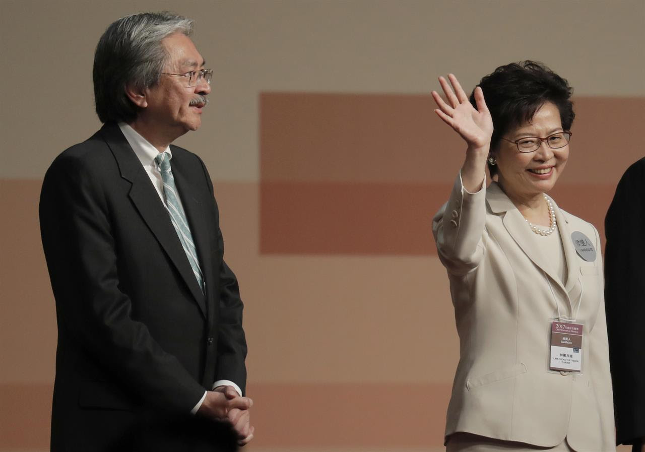 Former Hong Kong Chief Secretary Carrie Lam, right, declares her victory in the chief executive election of Hong Kong next to former Financial Secretary John Tsang in Hong Kong, Sunday, March 26, 2017. A Hong Kong committee has chosen the government's former No. 2 official Lam to be the semiautonomous Chinese city's next leader.
