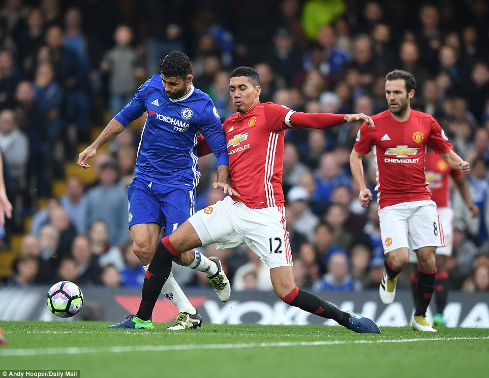 Chelsea's Diego Costa (left) is challenged by  Chris Smalling as Juan Mata looks on
