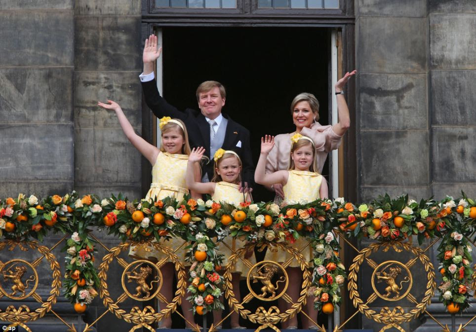 New beginnings: Dutch King Willem-Alexander and Queen Maxima appear on the balcony of the Royal Palace with their children, from left: Catharina-Amalia, Ariane, and Alexia