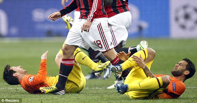 Rolling around: Messi (left) and Daniel Alves (right) lie on the pitch