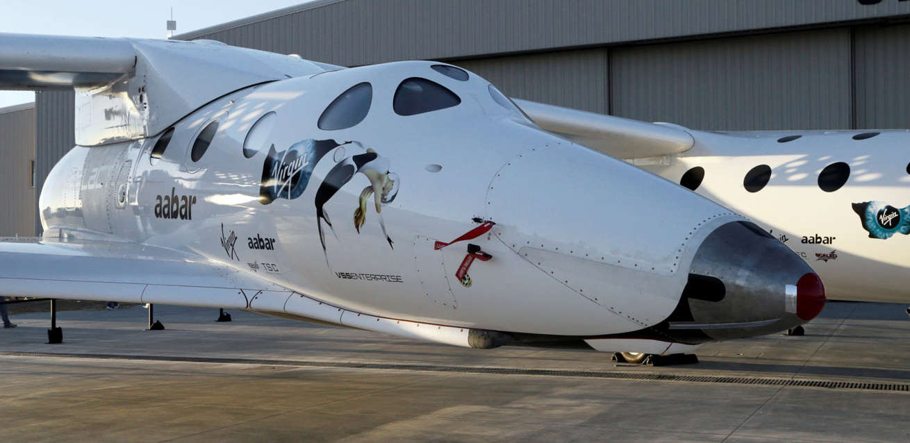 SpaceShipTwo is seen mounted under its mother ship White Knight at a Virgin Galactic hangar at Mojave Air and Space Port in Mojave, Calif., Wednesday, Sept. 25, 2013.