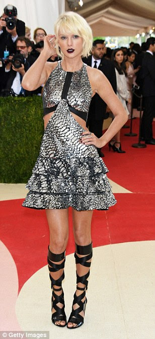 Vision of the future:Taylor Swift stuns in futuristic silver Louis Vuittonmini-dress with cutaway design as she leads the red carpet at the Met Gala in New York on Monday
