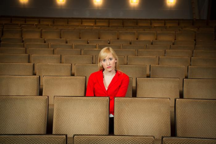 A woman alone in a theater.