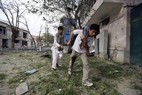 Men carry a wounded Afghan policeman away from the site of an explosion in Kabul, May 24, 2013. REUTERS-Omar Sobhani