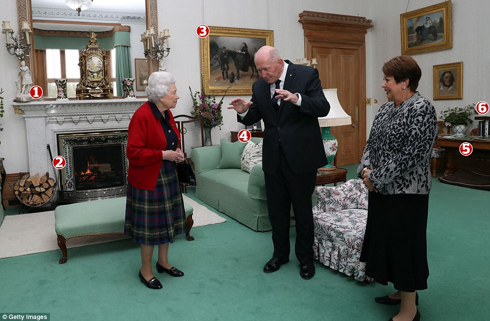 Timeless elegance: The Queen with Sir Peter Cosgrove, Governor General of Australia, and Lady Cosgrove in the drawing room at Balmoral Castle today Pictured: 1. A set of white figurine candlestick holders that are believed to have been used by Queen Victoria in the mid-1800s; 2. A fireplace trim featuring a repeating thistle motif in a nod to Scotland's national flower; 3. A painting of Queen Victoria and her trusted ghillie John Brown at Osborne House on the Isle of Wight; 4. An iPod classic and iPod dock speaker, which could have possibly been gifted by President Obama; 5. A selection of magazines, including the most recent issue of Country Life; 6. Wooden elephant bookends, a possible nod to Prince Harry's personal passion