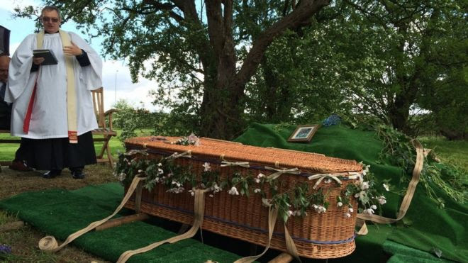 A wicker coffin being buried in woodland