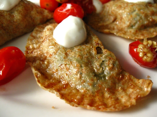 Spinach and Eggplant Pierogi Topped with Roasted Grape Tomatoes and Yogurt Sauce