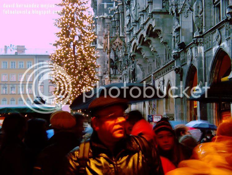 Escena de gente caminando en la plaza central de Municht, Alemania, mientras está lloviendo, con un mercadillo navideño y un árbol decorado con luces