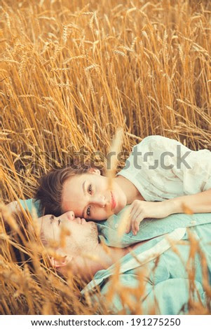 Young couple in love outdoor.in summer in field.Couple hugging.Young beautiful couple in love staying and kissing on the field on sunset. Soft sunny colors. Beautiful couple lying on the glass