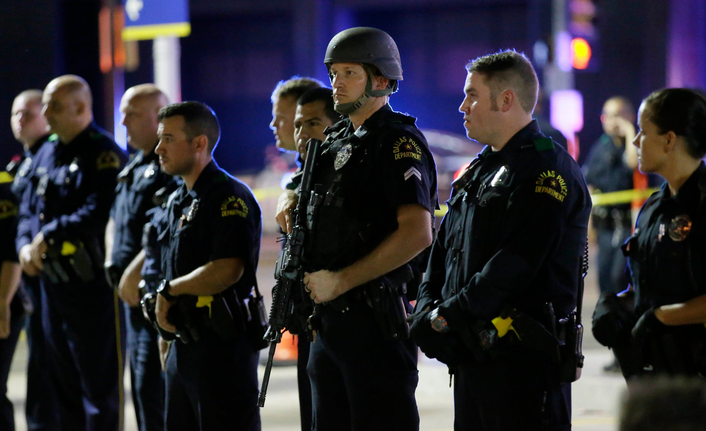 Dallas police officers stand in a line near the site of shootings in downtown Dallas, early Friday, July 8, 2016. Snipers opened fire on police officers, police said; some of the officers were killed.