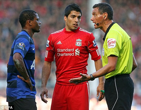 Flashpoint: Referee Andre Marriner talks to Liverpool striker Luis Suarez (centre) and Manchester United defender Patrice Evra during the clash at Anfield