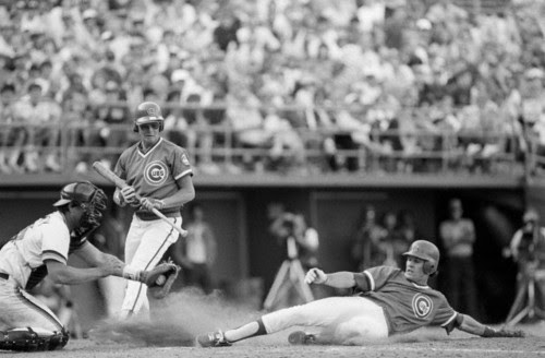 Chicago Cubs Ryne Sandberg slides and steals home against San Diego Padres catcher Terry Kennedy. Cubs batter Tom Veryzer steps out of the way. (1984)