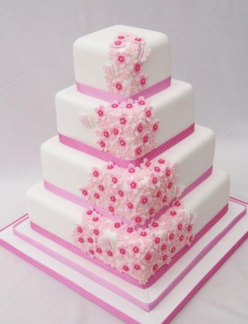 Four tier square white wedding cake with pink flowers and ...