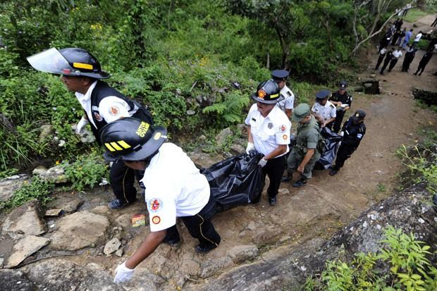 Bombeiros voluntários carregam alguns dos corpos (Foto: AFP)