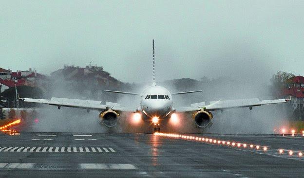 Imagen de un Airbus A-319 de la compañía Vueling maniobrando sobre la pista del aeropuerto de Hondarribia un día lluvioso.