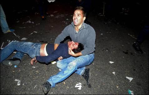 Un manifestante sostiene a un compañero insconsciente tras ser golpeado por la Policía durante la manifestación del 25 de septiembre de 2012 frente al Congreso de los Diputados.