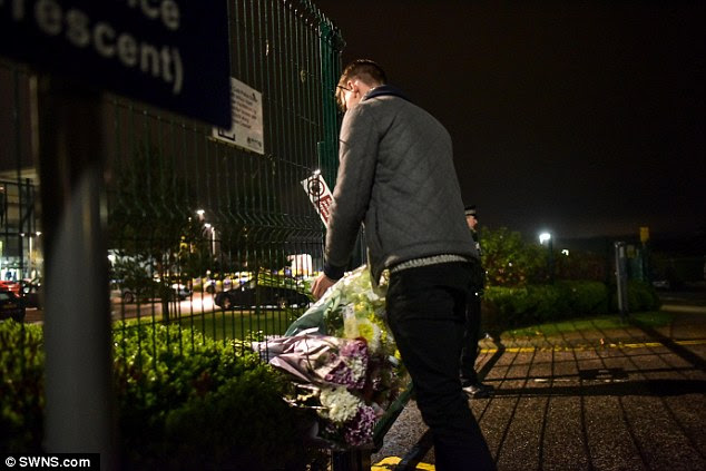 A boy lays flowers at the gates of Cults Academy following the tragic incident at the Aberdeen school