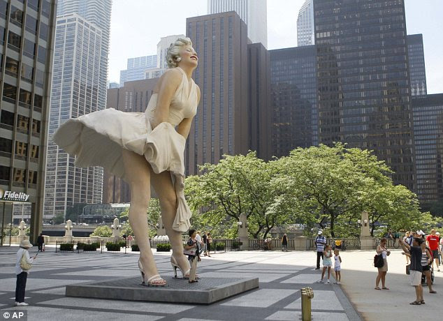 People gather around Seward Johnson's 26ft-tall sculpture of Marilyn Monroe, in her most famous wind-blown pose, on Michigan Avenue, in Chicago