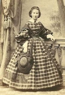 1861-1865, Lovely plaid dress with really full sleeves & undersleeves; solid sleeve caps that extend to bodice center like low lapels and a wonderful hat!  Love this design.  (The small dainty figure helps!)