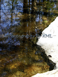 ice melting around the rocks at the lake