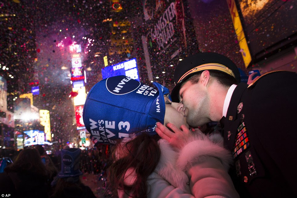 Reason to celebrate: Newly-engaged Sonja Babic, 30, of Texas, and National Guardsman John Cebak, 27, of Kentucky, share a kiss in Times Square at midnight
