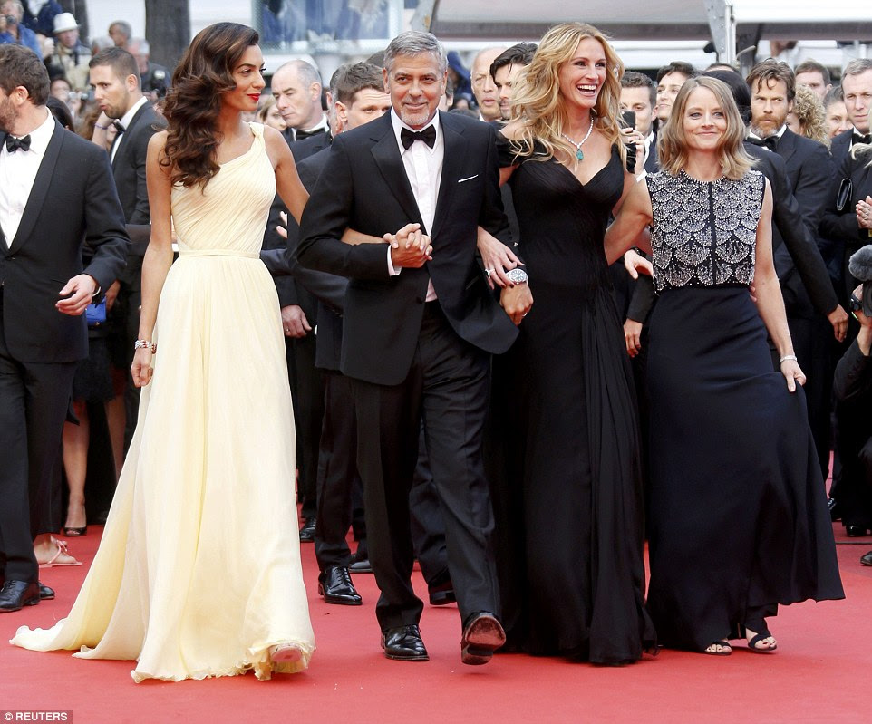 All together now: The actress put on a united front with her co-star George, his wife Amal and director Jodie Foster, linking arms as they ascended the steps of the iconic venue