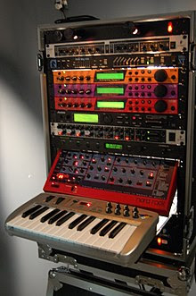 Several rack-mounted synthesizers that share a single controller