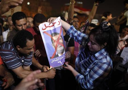 Protesters light a poster of President Mohamed Mursi on fire in Tahrir square as they listen to Mursi's public address, in Cairo June 26, 2013. REUTERS/Asmaa Waguih