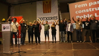 El secretariat de Poble Lliure canta Els Segadors amb el braç alçat durant l'assemblea nacional a les Cotxeres de Sants (ACN)