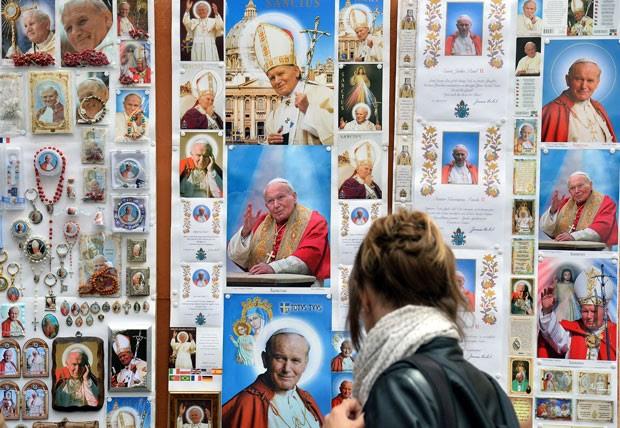 Mulher passa por posteres e cartões postais com a imagem do Papa João Paulo II em Roma (Foto: Stefano Rellandini/Reuters)