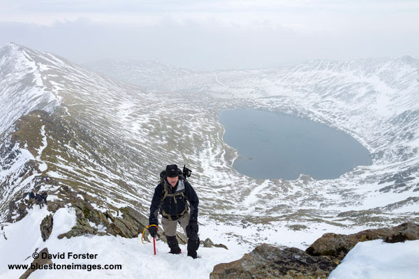 01M-9073 Hill Walker with Ice Axe on Swrirral Edge with Red Tarn Below Lake District Cumbria UK