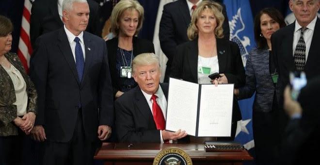 El presidente de EEUU, Donald J. Trump, enseña la firma de la orden ejecutiva para destinar fondos federales a la construcción del muro con México. - EFE