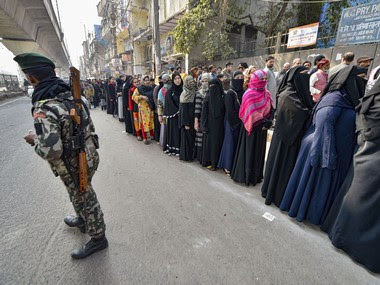 A security personnel stands guard as voters stand in a queue to cast vote during the Delhi Assembly election. PTI